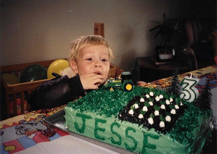 Jesse as a child on his birthday with a tractor cake