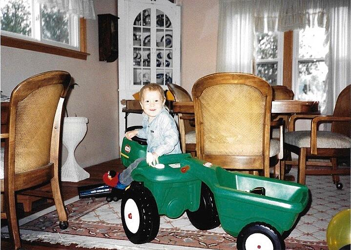 Jesse as a child playing in a toy tractor