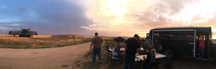 The Jessens and their employees gather for a field side dinner during wheat harvest
