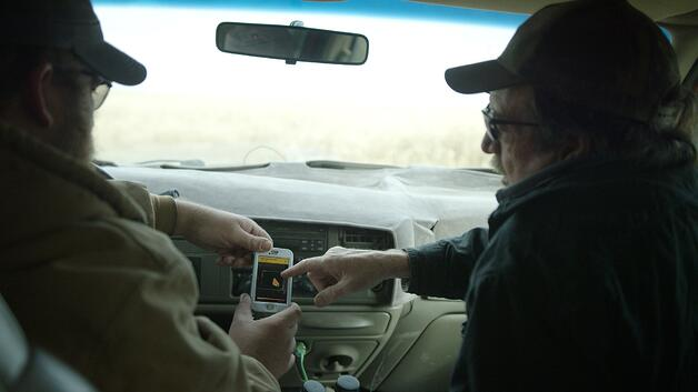 farmers in the truck looking at satellite imagery
